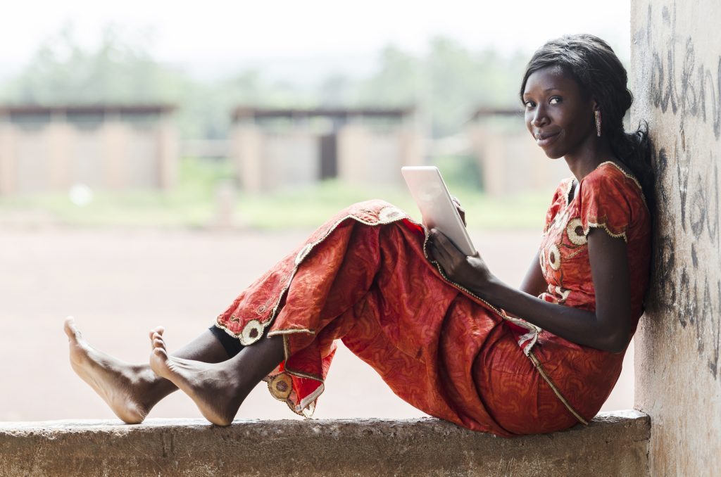 Street Shot of an African Ethnicity young woman working on business holding her technology item in a university in Bamako, Mali. University classroom class high school environment.